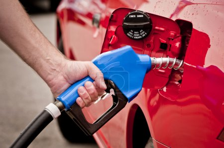 Man Using Blue Gasoline Nozzle In Red Car