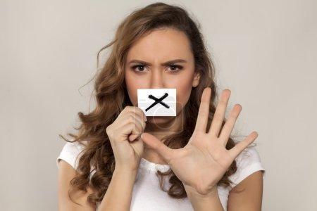 Foto de Nerviosa joven con X signo dibujado en un papel sobre su boca - Imagen libre de derechos