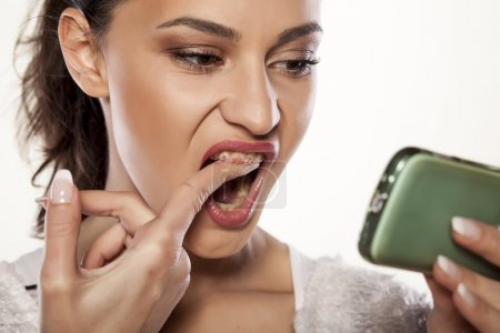 Photo for Young girl erasing lipstick from her teeth with her finger - Royalty Free Image