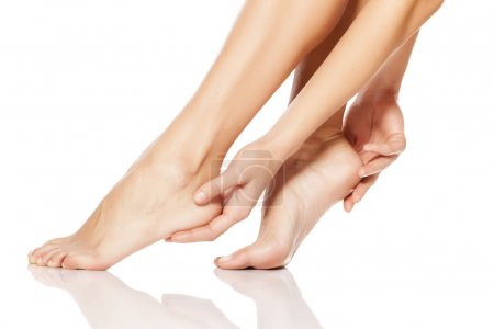 Photo pour Femme toucher tendrement ses pieds - image libre de droit