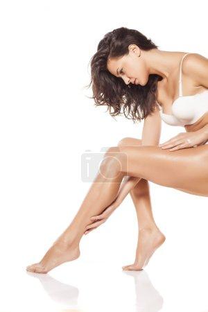 Photo pour Belle jeune femme, appliquer la lotion pour le corps sur ses jambes - image libre de droit