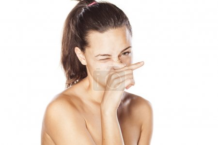 Young girl rubbing her nose on white background...