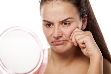 Photo pour Jeune femme insatisfaite devant un miroir - image libre de droit