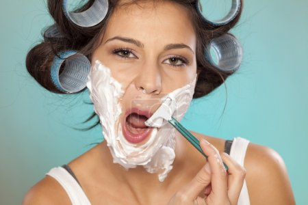 Woman shaving her face