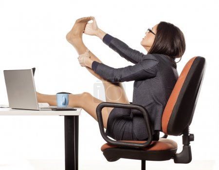 Photo for Businesswoman with her legs on the table massaging her foot - Royalty Free Image