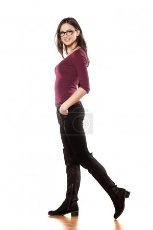 Photo for Side view of a pretty young woman, walking on white background with her hands in her pockets - Royalty Free Image