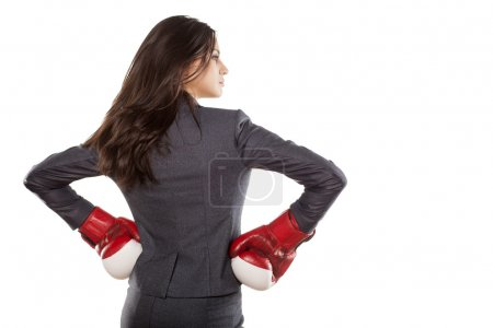 Back view of a business woman with boxing gloves o...