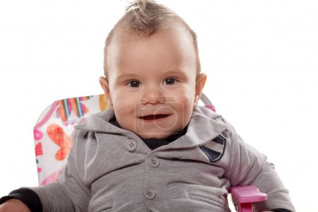 Photo for Cute smiling baby boy sitting on a chair - Royalty Free Image