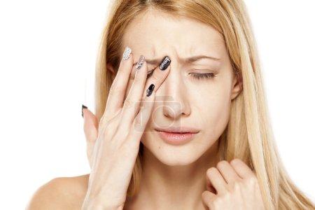 Photo pour Jeune blonde avec des yeux douloureux sur fond blanc - image libre de droit