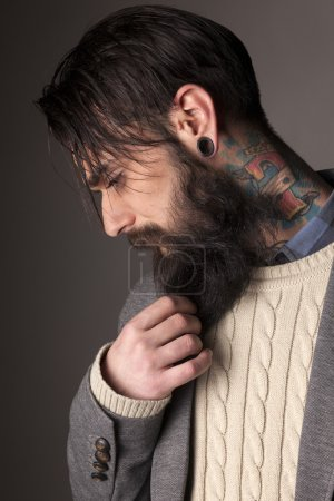 Photo pour Jeune homme avec une longue barbe, les tatouages et le perçage des oreilles posant en studio sur fond gris - image libre de droit
