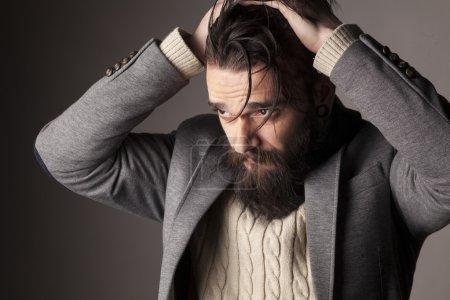 Foto de Retrato de un triste hombre joven con barba y bigote y sus manos en su pelo - Imagen libre de derechos