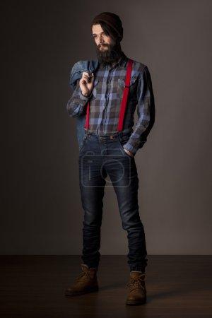 Photo pour Jeune homme barbu tenant une veste en denim - image libre de droit