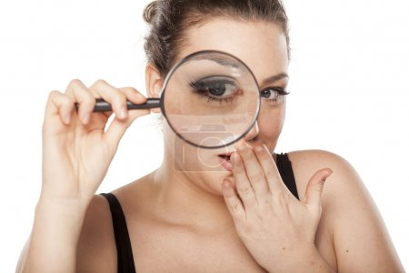 Photo for Amazed young woman looking through a magnifying glass - Royalty Free Image