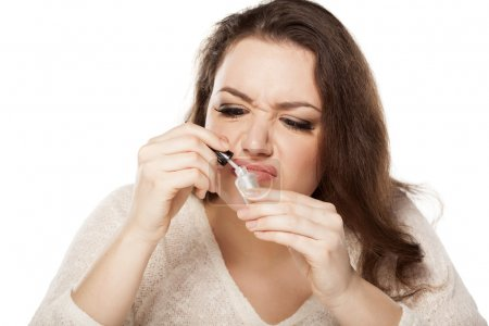 Young woman is disgusted by the smell of nail poli...
