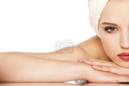 Foto de Media cara de una hermosa mujer con una toalla en la cabeza acostada sobre blanco - Imagen libre de derechos