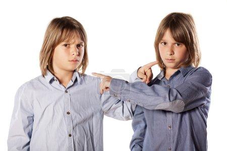 Foto de Dos gemelos a hermanos señalar con dedo el uno al otro - Imagen libre de derechos