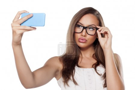 Pretty girl with glasses and pursed mouth making s...