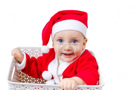 Funny boy in Santa Clause suit sitting in a box