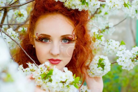 Photo for Portrait of beautiful woman with clean skin looking through spring cherry flowers - Royalty Free Image