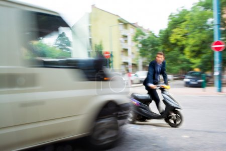 Dangerous city traffic situation with a motorcyclist and a bus