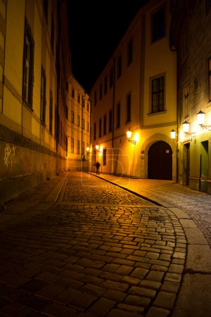 Man walking around the  street of the old town at night in Pragu