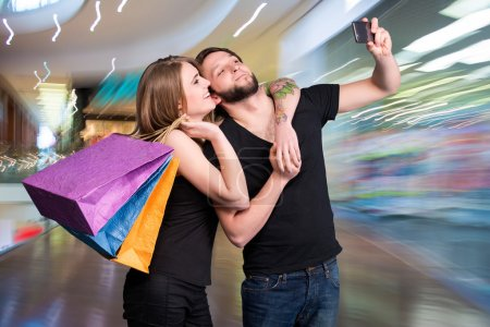 Happy couple with shopping bags taking selfie