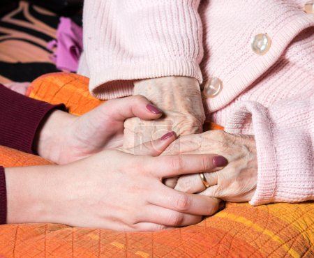 Photo pour Des mains bienveillantes tenant les mains de la vieille dame à la maison - image libre de droit