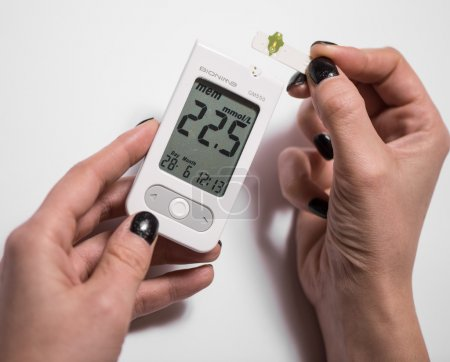 young woman checking blood sugar level