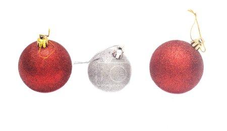 Photo pour Ligne de deux boules de Noël rouges et une d'argent isolées sur fond blanc - image libre de droit