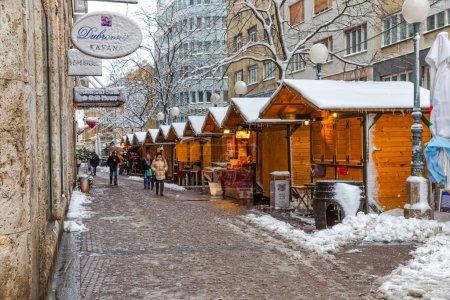 Foto de ZAGREB, CROATIA - December 28, 2014: Winter scene of the people walking in front of the wooden houses of the Christmas fair in Gajeva street - Imagen libre de derechos