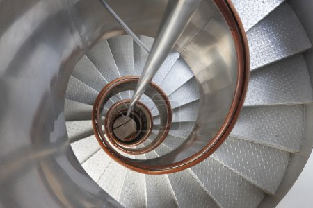 Metallic spiral stair with wooden handrails inside a lighthouse