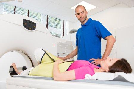 Photo pour Assistante technique médicale conseillant le patient et préparant le scan de la colonne vertébrale avec tomodensitométrie par rayons X CT en radiologie - image libre de droit