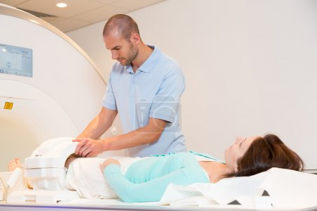 Medical technical assistant preparing scan of knee with MRI