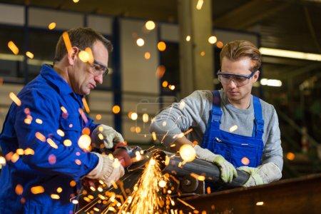 zwei Arbeiter arbeiten mit Winkelschleifer