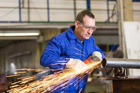 Steel construction worker grinding metal with angle grinder