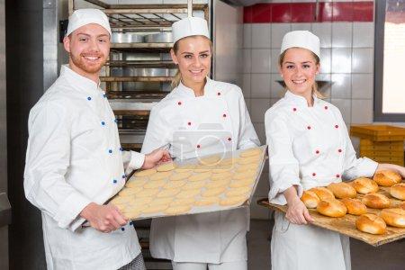 Bäcker präsentiert Blech mit Gebäck oder Teig beim Bäcker