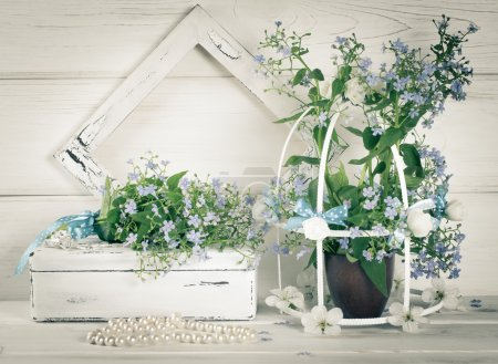 Forget-me-not flowers with birdcage and photo frame and casket w