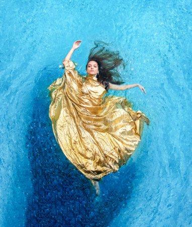 Vista superior de una hermosa mujer sexy joven en vestido de oro, vestido de noche, toalla flota sin peso elegantemente nadando en el agua de la piscina de spa