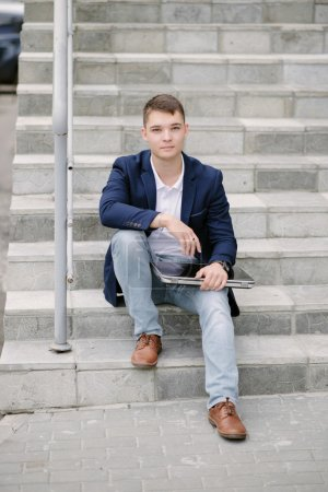 Portrait of a young businessman sitting with notebook on stairs.