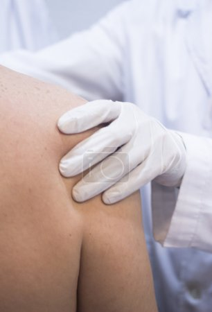 Dooctor surgeon examines patient shoulder arm injury