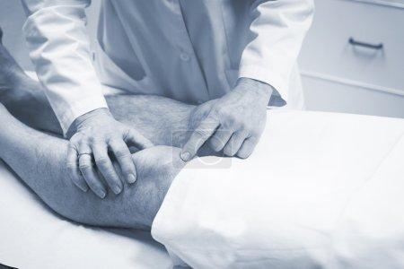 Traumatologist orthopedic surgeon doctor examining patient