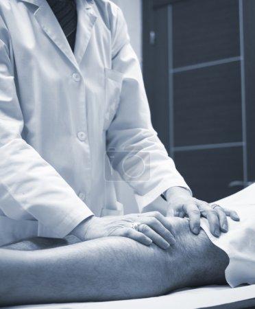Photo pour Médecin orthopédiste de traumatologue examinant le patient d'homme moyen d'âge pour déterminer la blessure, la douleur, la mobilité et pour diagnostiquer le traitement médical dans la jambe, le cartilage de ménisque de genou, la cheville et la blessure de pied. - image libre de droit