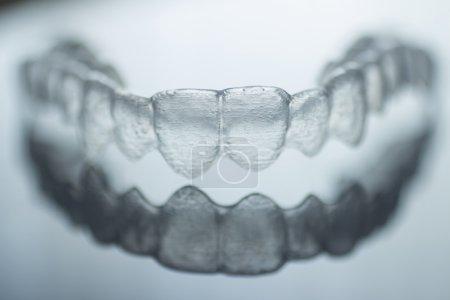 Photo pour Supports de plastique dentaire dents Invisalign invisibles dent accolades isolés avec faible profondeur de photographie artistique de mise au point. - image libre de droit