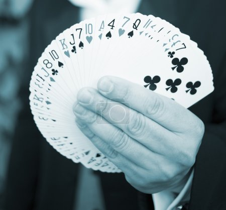 Playing cards spread out in hand of magician photo...