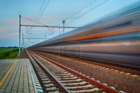 Photo for Railroad travel and transportation industry business concept: summer night view of high speed passenger train departing from railway station platform with motion blur effect - Royalty Free Image