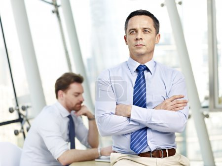 contemplating business person sitting on desk in office