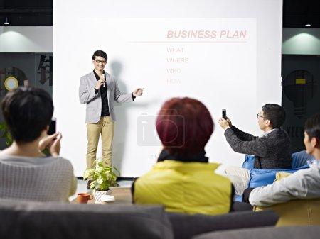 jeune homme asiatique présentant le plan d'affaires