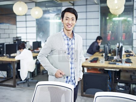 Photo for Confident young asian entrepreneur standing in own company with laptop computer looking at camera smiling. - Royalty Free Image