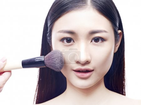young asian model applying foundation make-up