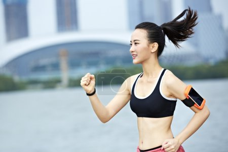 young asian woman running by a lake